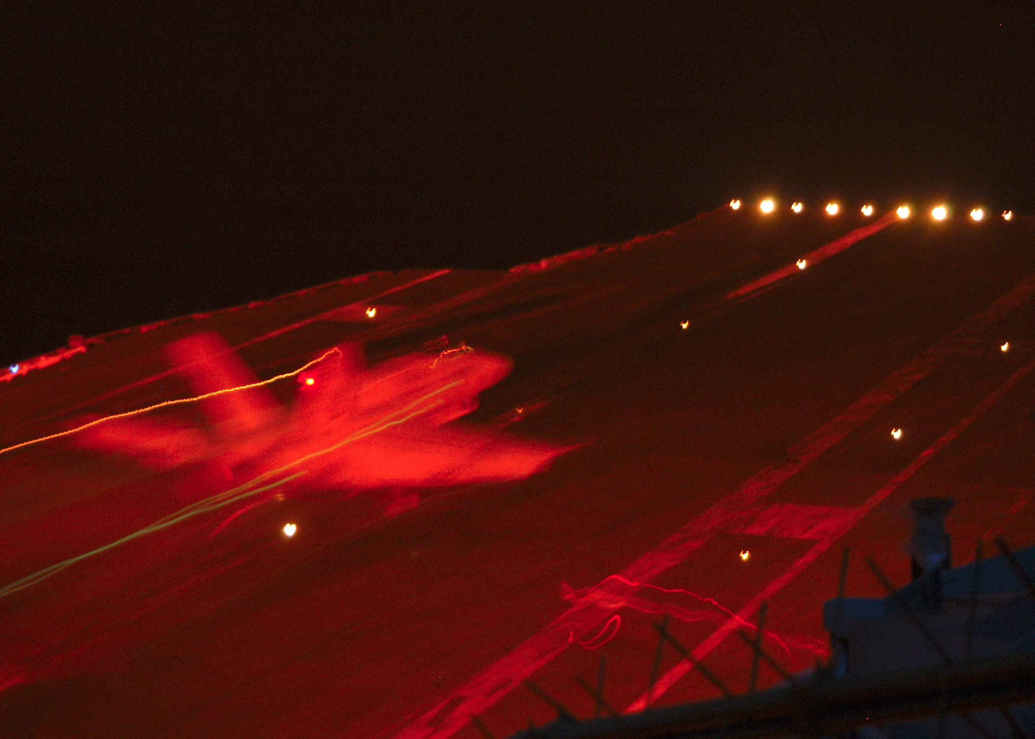 Us navy 040104 n 7408m 006 an f a 18 hornet assigned to carrier air wing one cvw 1 catches the wire during an arrested landing on the flight deck during night flight operations aboard uss enterprise cvn 65